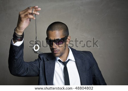 Sharp modern man looks at his old pocket watch - stock photo