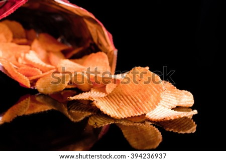 sharp potato chips poured out of the pack - stock photo