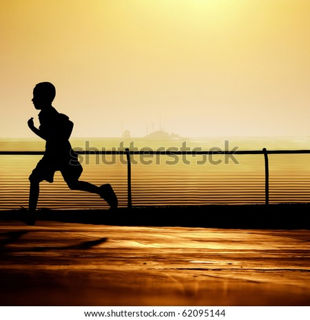 Sharp silhouette of a boy running with a beautiful sunset in the background. - stock photo