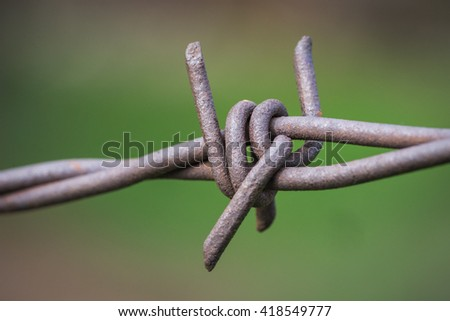 Sharp twisted metal barbs of barbed wire fence line. - stock photo