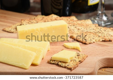 Sharp white cheddar cheese with crackers and wine, shallow DOF focus near front - stock photo