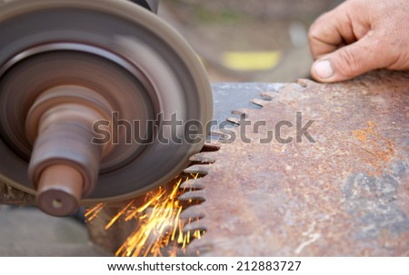 sharpening saw by abrasive disk machine  - stock photo