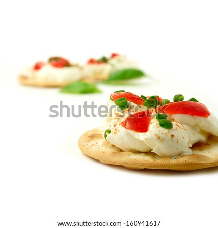 Sharply focused macro of fresh cream cheese and tomato canape against a white background. Copy space. The perfect image for a restaurant snack menu or summer party invitation cover design. - stock photo