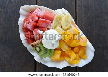 Shaved ice dessert with fresh fruit in the shell - stock photo