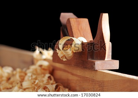 shaving and wooden plane on a black background - stock photo