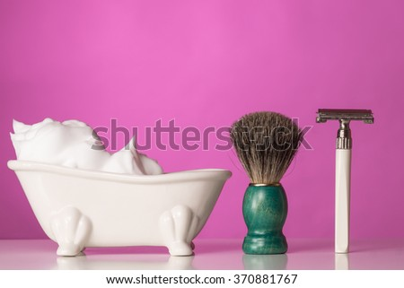 Shaving Equipment on wooden Table and pink Backdrop - stock photo