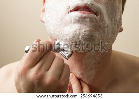 Shaving under his chin a man is getting clean for the day. He us using a double edged safety razor - stock photo