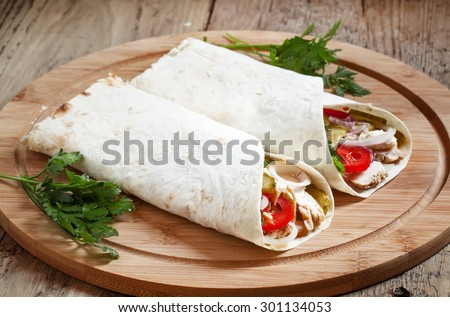 Shawarma, turkish doner kebab, roll with meat and pita bread on a wooden background, selective focus - stock photo