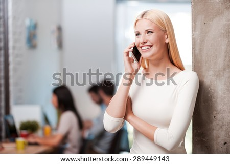 She is always in touch. Happy young blond hair woman talking on the mobile phone and smiling while her colleagues working in the background - stock photo