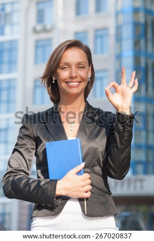 She is Okay and she show that. Portrait of beautiful businesswoman with Okay gesture - stock photo