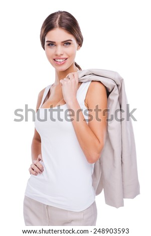 She is pleased with herself. Confident young businesswoman carrying her jacket on shoulder and smiling while standing against white background - stock photo