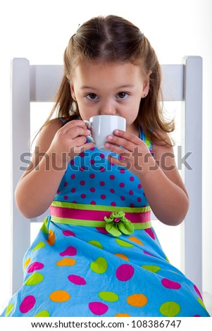 She is sitting on the chair carefully drinking the coffee.9 - stock photo