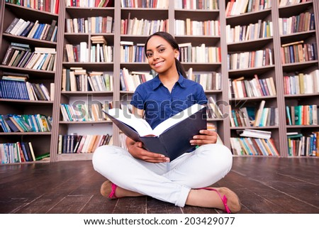 She loves reading. Beautiful African female student holding a book and smiling at camera while sitting on the floor in library - stock photo