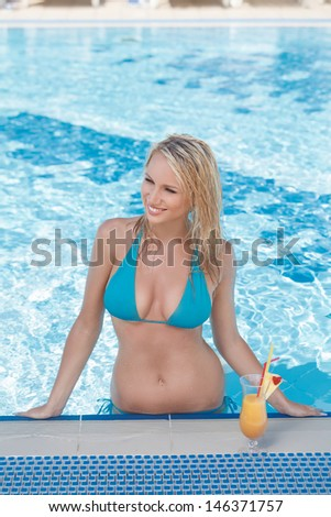 She loves swimming. Beautiful young women sunbathing while standing in the pool - stock photo