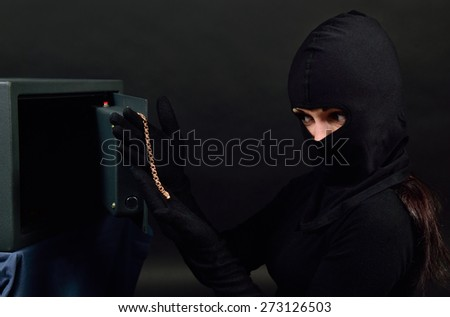 She opened the safe and found a gold chain - stock photo