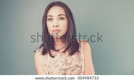 She pays no attention to you. Vintage, retro style of portrait of Asian woman in pink vintage dress on blue - green background. - stock photo