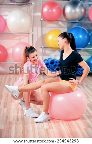 She uses pilates balls in every class. Attractive young woman leading fitness class and helping her student in stretching while sitting on fit ball at health club - stock photo