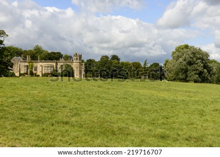 sheep grazing in Abbey park , Lacock landscape with flock of sheep grazing on meadows of Abbey park,shot in bright light from the public street in  historic touristic village of Wiltshire  - stock photo