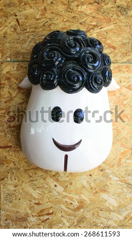 Sheep head decoration on wood wall - stock photo
