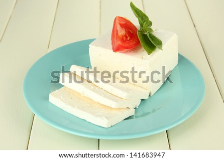 Sheep milk cheese, with basil and tomato on color wooden background - stock photo