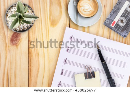 Sheet music, cactus, fountain pen, tape cassette and coffee latte on wooden table - stock photo