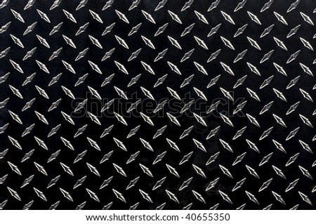 Sheet of black diamond plate with highlighted texture - stock photo