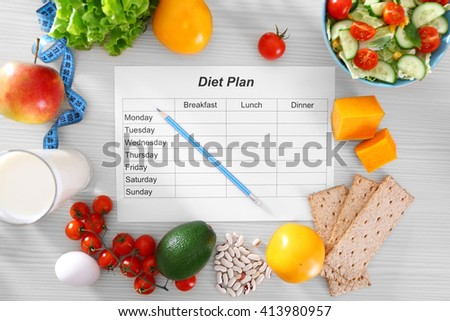 Sheet of Diet Plan and fresh products on wooden table, top view - stock photo