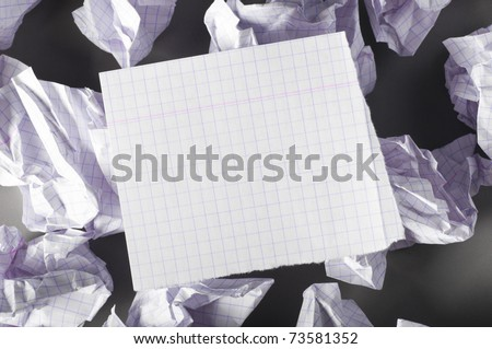 sheet of paper and crumpled wads on table. - stock photo