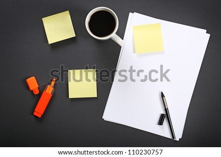Sheet of paper, pen, cup of coffee and other office equipment on black office table. - stock photo