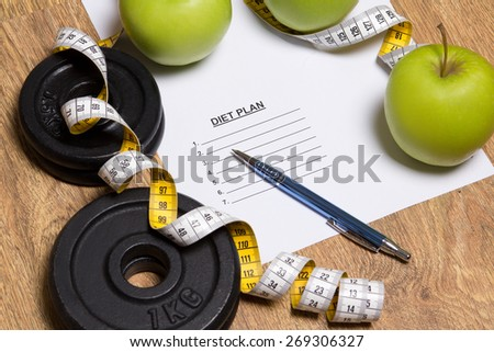 sheet of paper with diet plan, apples and dumbbell on wooden background - stock photo