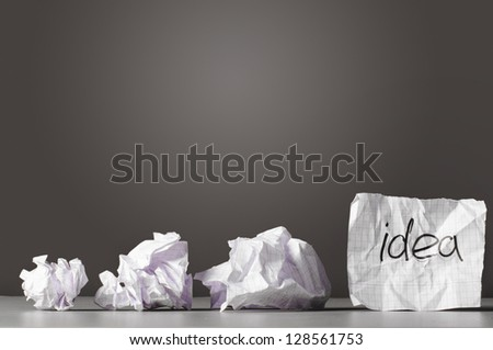 sheet of paper with word idea and crumpled wads on table. - stock photo