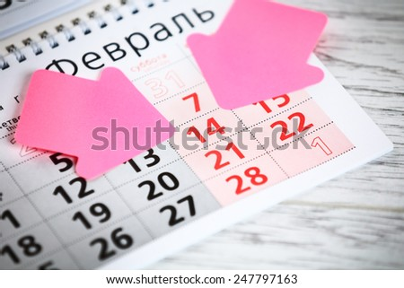 Sheet of wall calendar with pink arrows marks on 14 February - Valentines day - stock photo