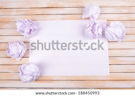 Sheet of white paper with crumpled  paper  and pencil on table close-up - stock photo