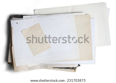 Sheet of yellowed and square graph paper on pile of aged papers - stock photo