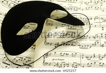 Sheetmusic With a Black Mask - Sheetmusic Background - stock photo