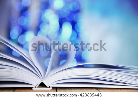 Sheets of book curved into heart shape on wooden table against unfocused lights - stock photo