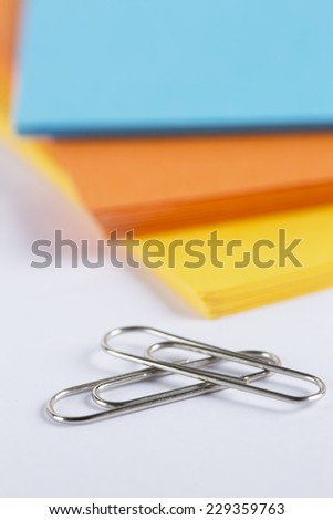 Sheets of coloured paper stacked on a white surface with stationary items - stock photo