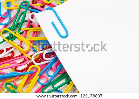 Sheets of whiter paper connected with blue staple against the multicolored paper clips - stock photo