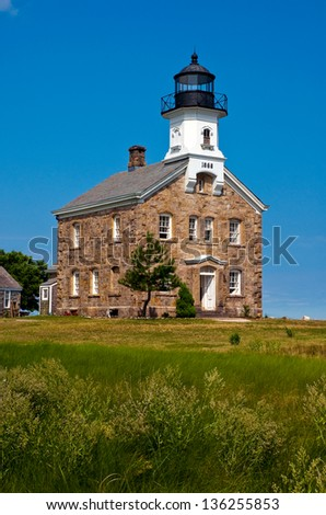 Sheffield Island lighthouse had a keeper who had cows that would cross over to nearby islands and become stranded, leaving the keeper to constantly try to keep the animals on the island. - stock photo