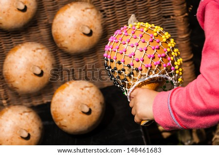 Shekere (gourd rattle) in child hand. Closeup. - stock photo