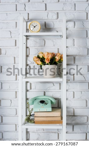 Shelf with interior decoration in front of a white brick wall, vintage decor - stock photo