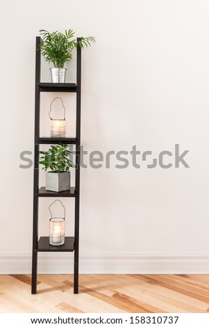 Shelf with plants and lanterns decorating a living room. - stock photo