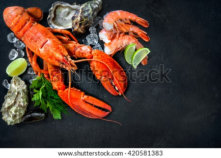 Shellfish plate of crustacean seafood with fresh lobster, mussels, shrimps, oysters as an ocean gourmet dinner background - stock photo