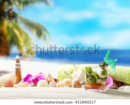 Shells, mojito and towel on sandy beach with tropical beach background  - stock photo