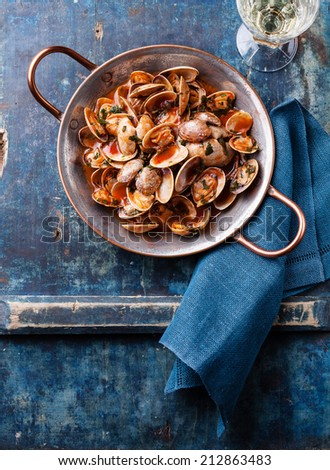 Shells vongole with parsley and tomato sauce and wine on blue background - stock photo