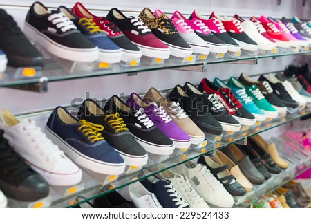 Shelves with casual shoes at  store - stock photo