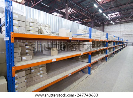 Shelving system with cardboard boxes in distribution warehouse. - stock photo