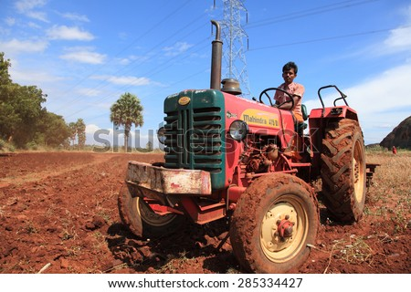 SHENGOTTAI, INDIA - SEP 25: An unidentified farmer in tractor prepare his farm land for cultivation on September 25, 2010 in a village in Shengottai, Tamil Nadu, India. - stock photo