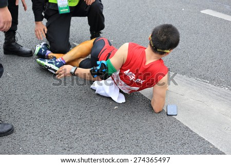 SHENZHEN,CHINA - DECEMBER 7: Medical support help a injured marathon runner's legs on the street at Shenzhen International Marathon DECEMBER 7, 2014 in Shenzhen, China  - stock photo