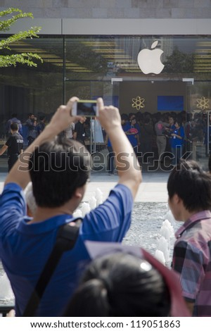 SHENZHEN, CHINA - NOV. 3: A man used iphone to take picture for the apple store. Apple open its seventh Apple store in mainland China, located in SHENZHEN, November 3, 2012. - stock photo